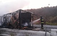 Carreta que carregava biscoitos tomba e pega fogo na BR-104