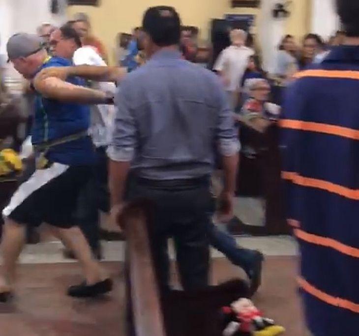 Homem sendo retirado pelos fiéis
