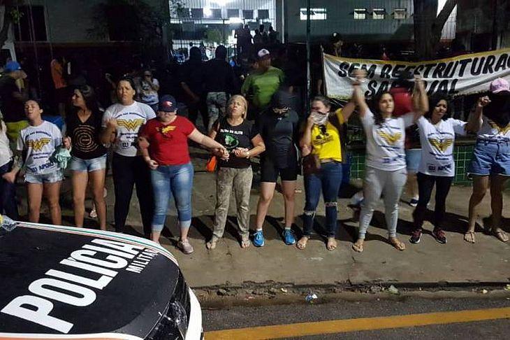 Mulheres de PMs fazem oração em frente ao 18° batalhão da Polícia Militar na noite de quinta-feira