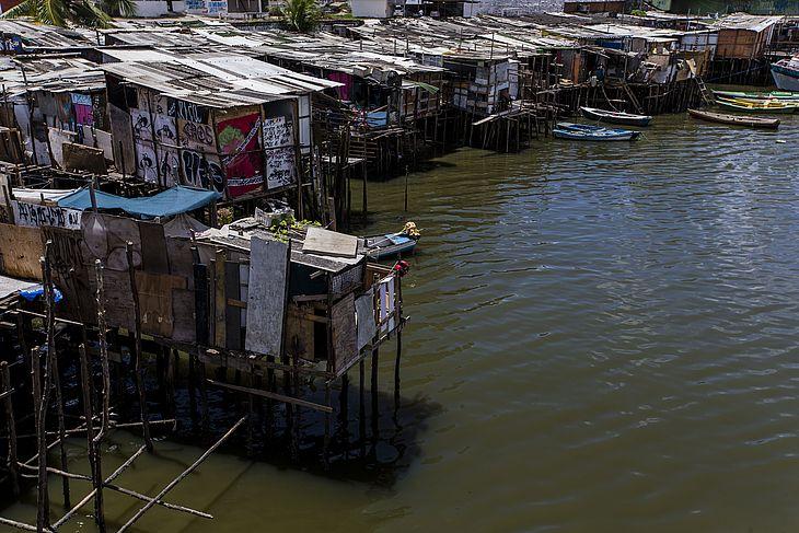 Palafitas construídas à margem do canal de mar que adentra pelo centro do Recife