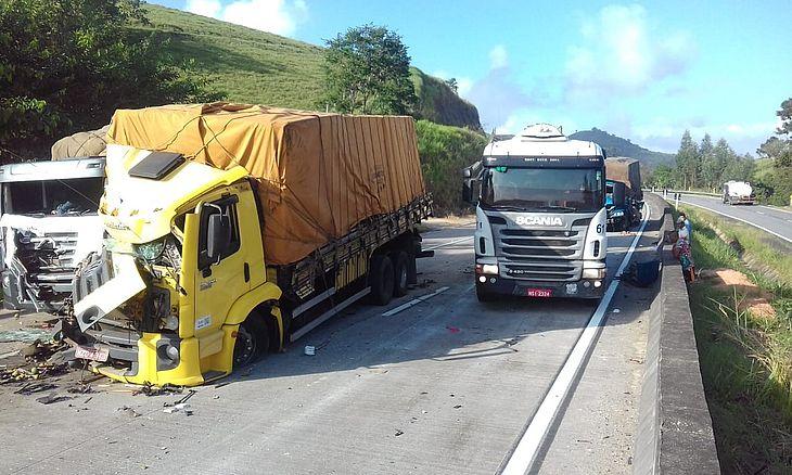 Foto mostra pelo menos três caminhões parcialmente destruídos em rodovia